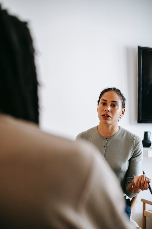 Concentrated ethnic female psychologist talking to client