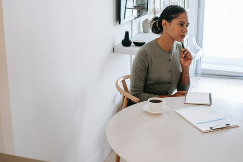 Concentrated ethnic female HR interviewer or psychologist in formal clothes sitting at round table with pen and notepad while looking away in contemplation