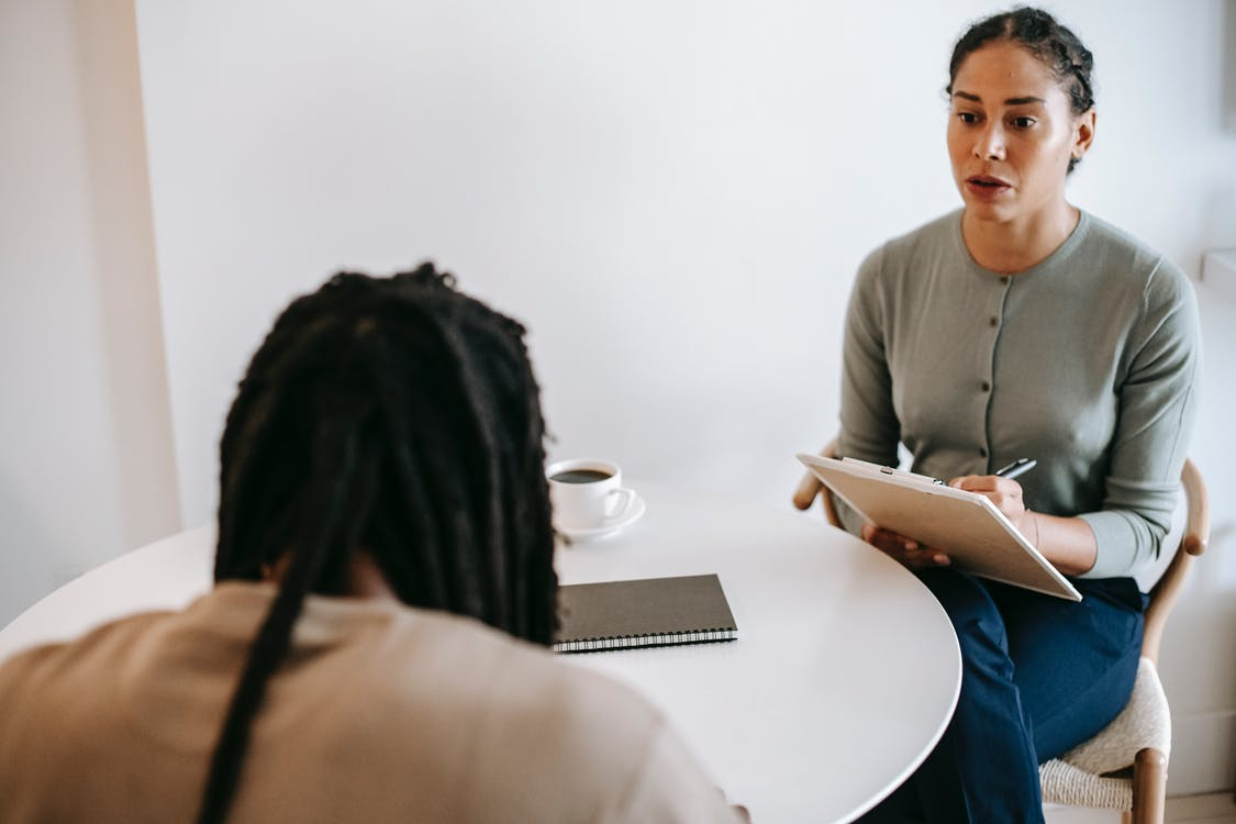 Focused ethnic female counselor wearing formal outfit sitting at table and discussing treatment method with male patient while taking notes in clipboard