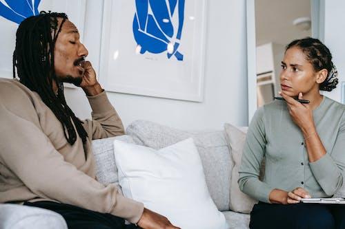 Serious ethnic female psychologist listening to black patient complaints