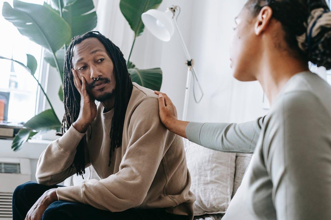 Ethnic psychologist touching black depressed clients shoulder