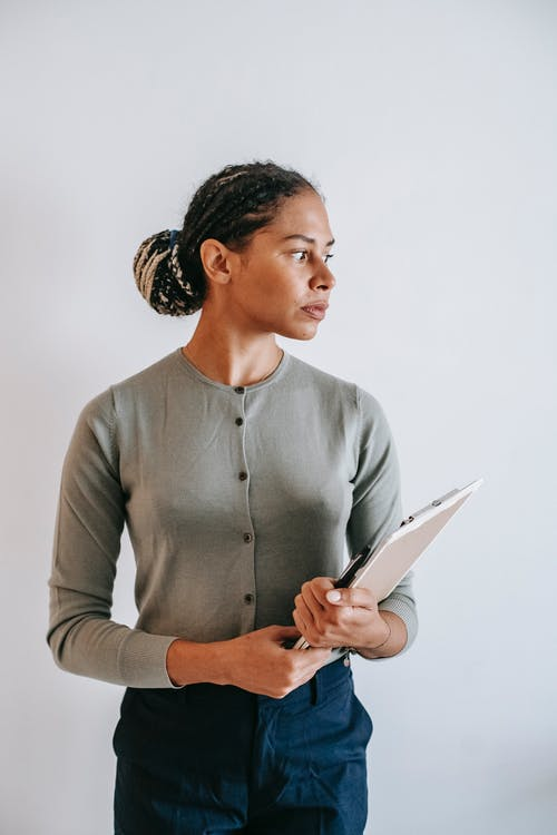 Serious ethnic female in formal wear with clipboard in hands standing against white wall and looking away in contemplation