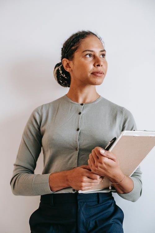 Pensive Hispanic woman standing with clipboard