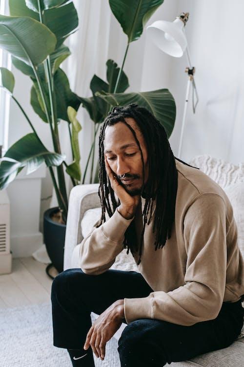 Black man resting on sofa in light room in daytime