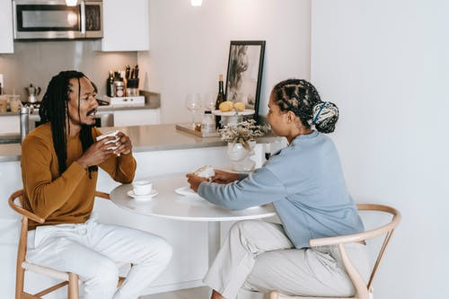 Positive diverse couple in casual clothes sitting at table with cup of drink and eating delicious food while spending time together in kitchen at home