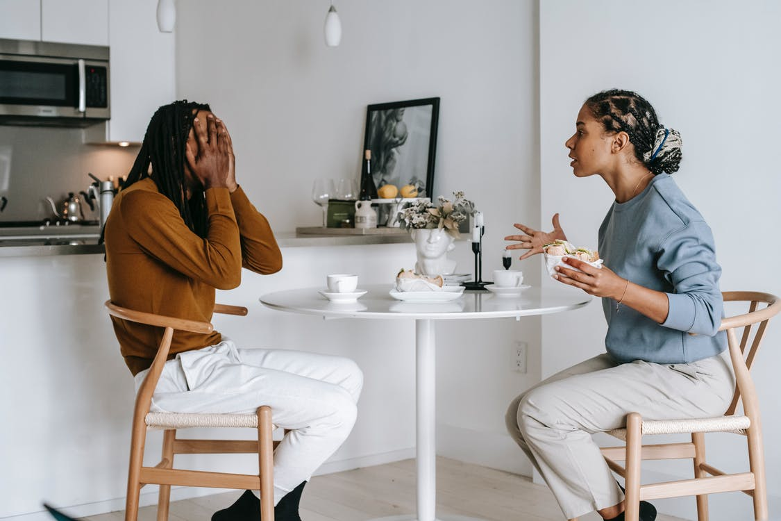 Side view of expressive Hispanic female in casual clothes arguing with African American boyfriend covering face with hands while sitting at table in kitchen at home
