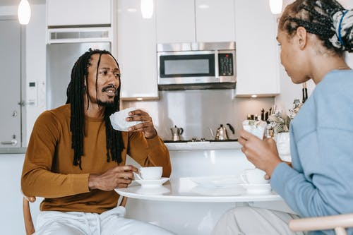 African American male in casual outfit with dreadlocks drinking coffee and eating sandwiches with African American female during breakfast in modern kitchen