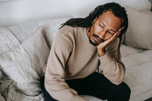 Pensive African American male with dreadlocks in casual clothes sitting on comfortable couch and pondering touching face