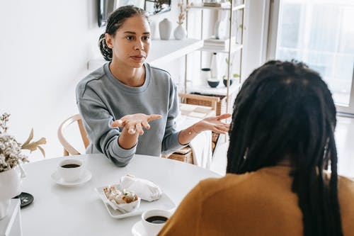 Young African American woman sitting at table and arguing with man in casual outfit in daylight