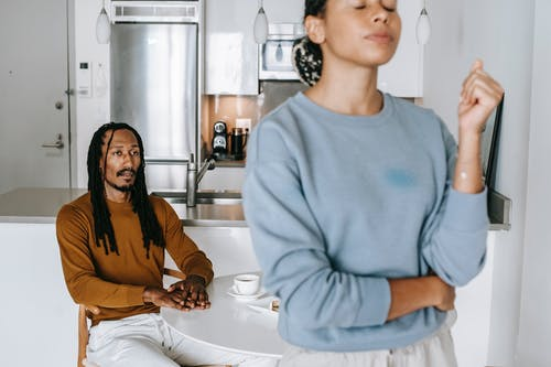 Young black man sitting at table while having conflict with standing near table woman in light kitchen