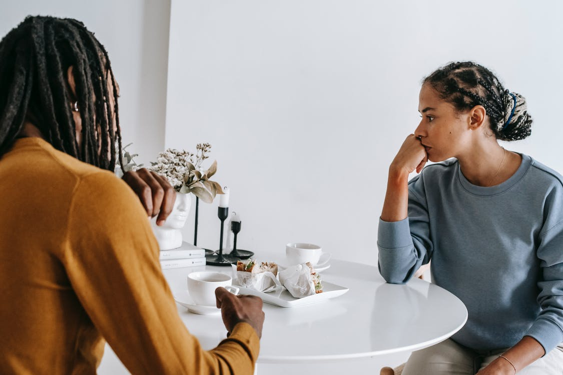 Young African American man sitting with woman at table and having conflict with each other at home