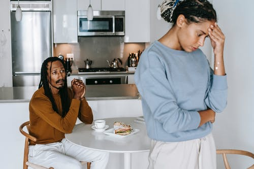 Young African American man sitting at table and arguing with woman while having breakfast at home