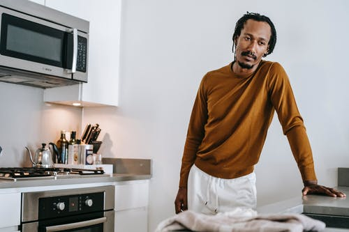 African American guy standing in kitchen at home