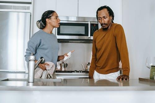 Black couple talking on kitchen