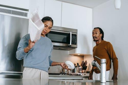 Черная дама и парень спорят на кухне