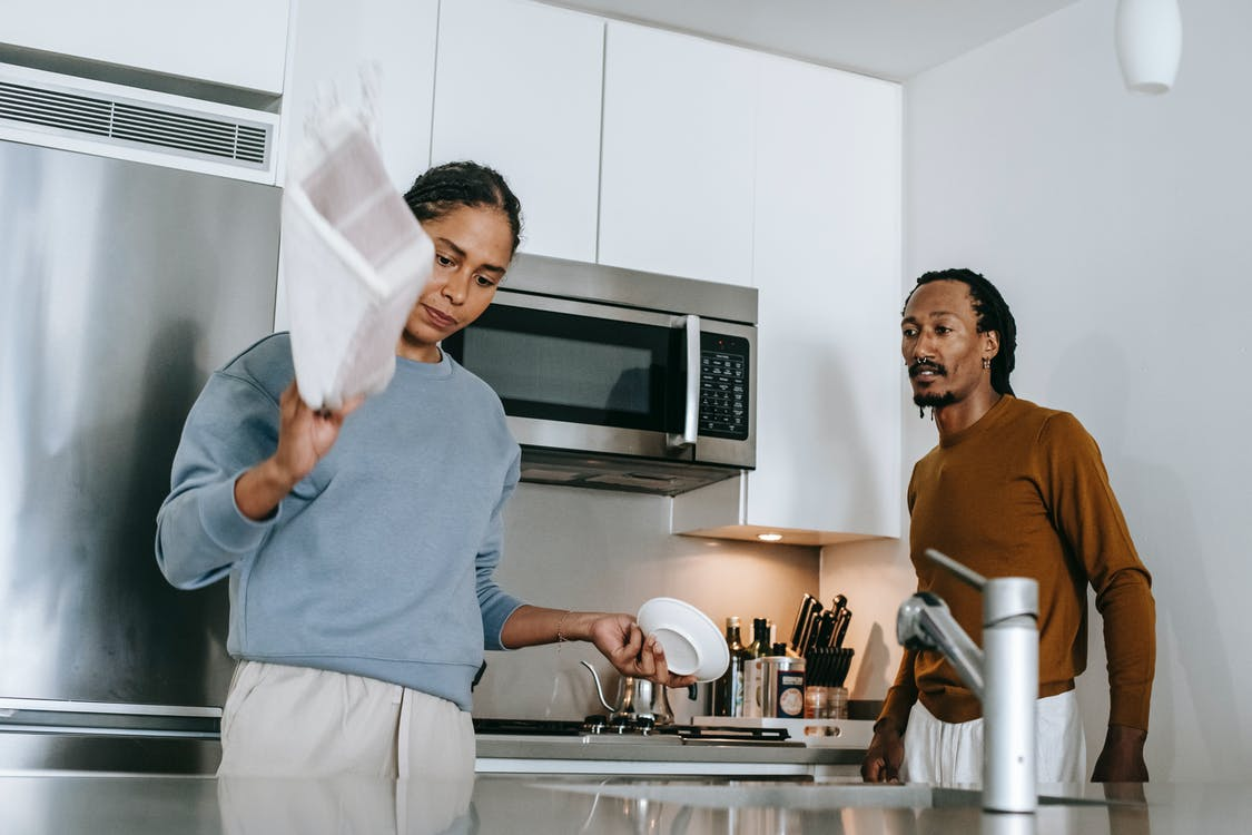 Black lady and guy arguing in kitchen