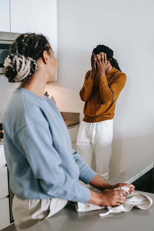 Young African American couple standing in room and arguing with each other while wearing casual clothes at home