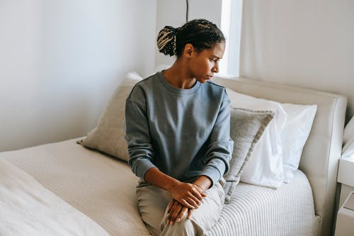 Black woman sitting on bed at home