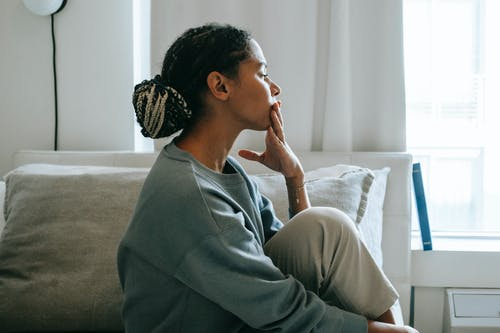 Side view young African American woman sitting on comfortable white bed and thinking in casual clothes in daytime