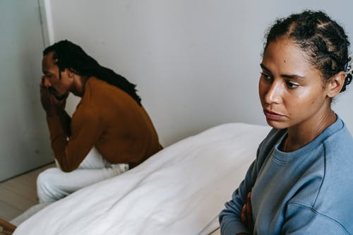 Young African American couple resting on bed and thinking while wearing casual clothes at home