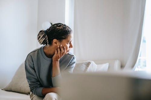 Afroamerikaner Dame, Die Auf Bett Im Hellen Raum Sitzt