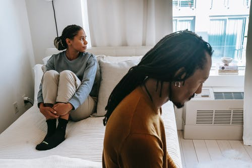 Young African American couple in casual clothes resting on bed with sad face in daytime