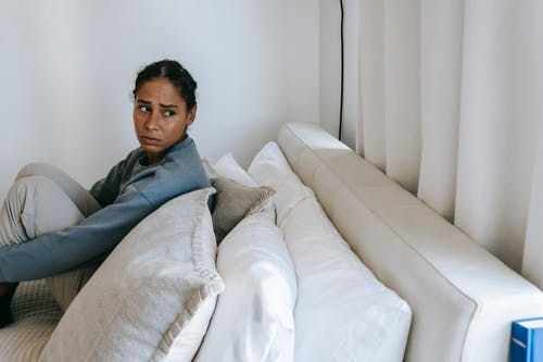 Sad young African American woman spending time on white bed and thinking in casual outfit while looking away at home