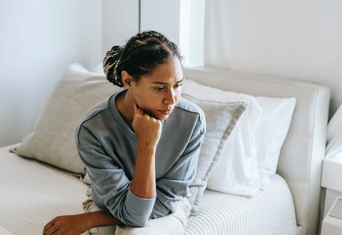 Black woman sitting on bed in light room