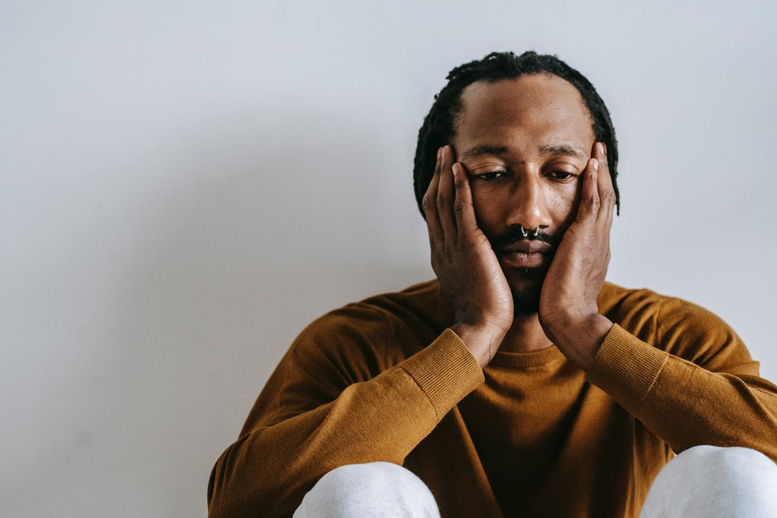 Unhappy black man touching face on light background