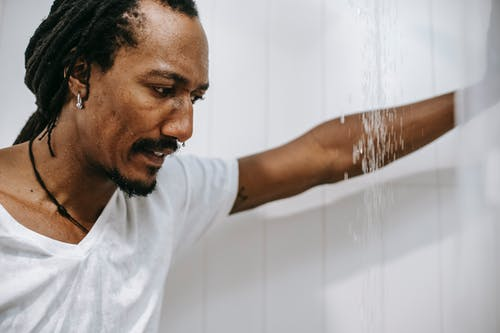 Side view of crop young worried African American man with dreadlocks in white t shirt leaning hand on tiled wall while standing under water stream in bathroom