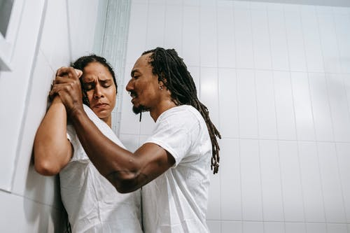 Side view of young black angered man with Afro braids in white t shirt pushing sad wife with closed eyes against tiled wall during conflict in bathroom