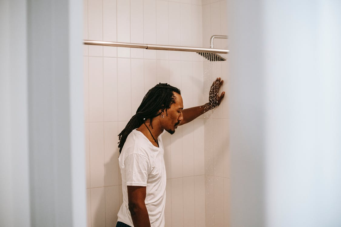 Frustrated ethnic man thinking about problems in bathroom