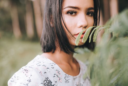 Attractive young woman near green tree