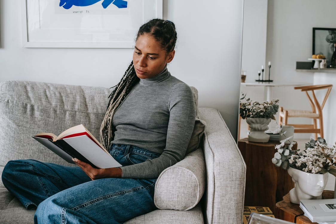Pensive young African American female with long braids in casual outfit relaxing on comfortable sofa and reading interesting book at home