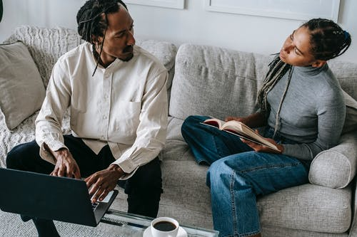From above of serious young African American husband and wife in casual outfits sitting on sofa with book and laptop and discussing relationships in cozy living room