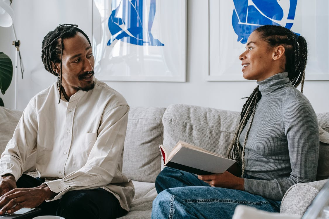 Positive young black lady with Afro braids sitting on sofa with interesting book in hands and speaking with boyfriend working remotely on laptop
