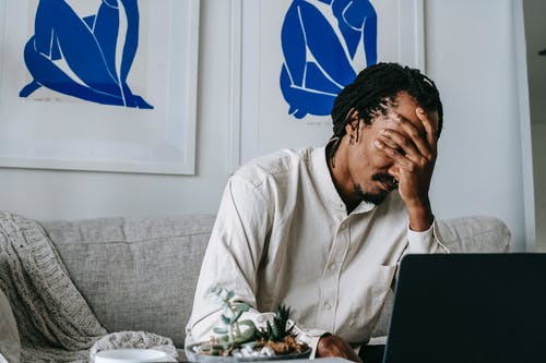 Frustrated young bearded African American male freelancer with dreadlocks in casual shirt working on laptop at home and covering eyes with hand after failure
