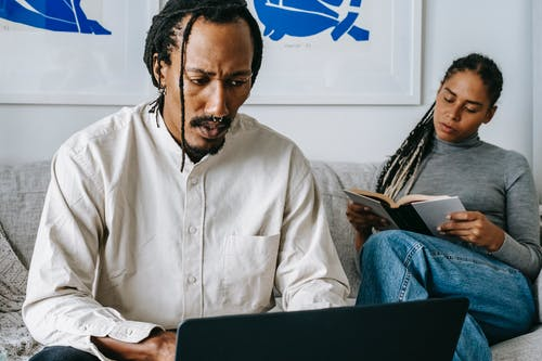 Serious African American man working on laptop sitting on sofa near reading wife