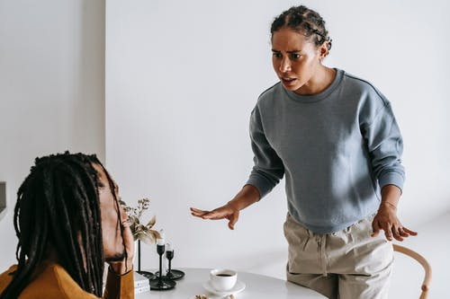 Serious young African American female in casual outfit standing near round table with cup of coffee and arguing with bearded husband