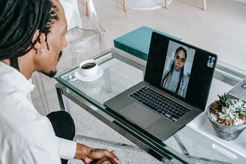 Young black guy having video chat on netbook with girlfriend