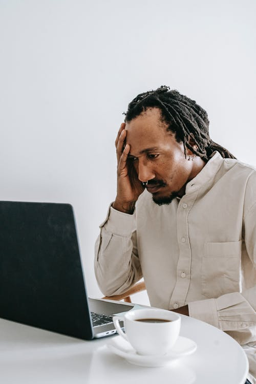 Worried young black man working online on laptop in kitchen