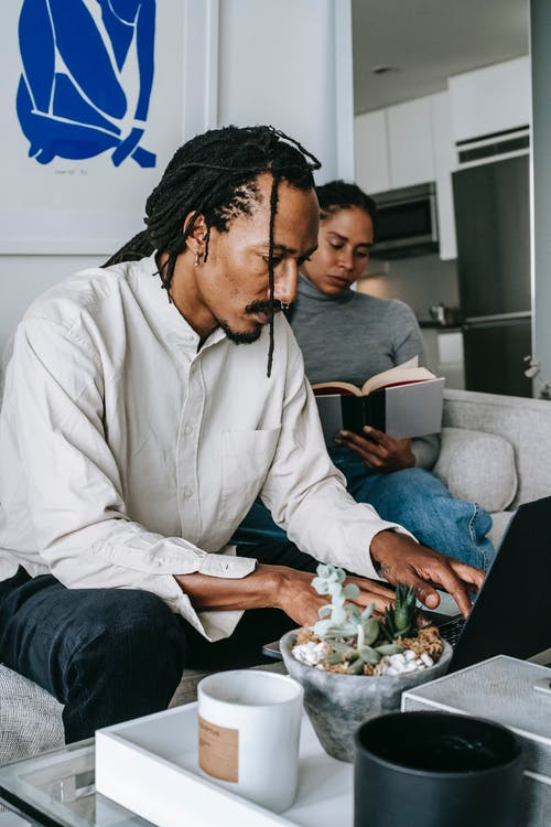 Focused young black couple using netbook and reading book in living room