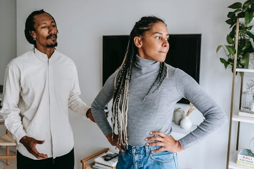 Unhappy African American couple quarreling while spending time together in light modern apartment