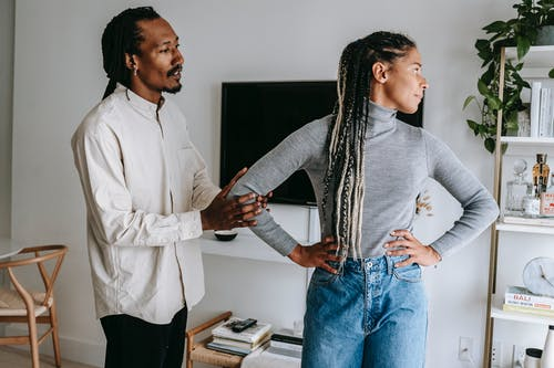 African American stylish man apologizing to sad girlfriend while having conflict at home