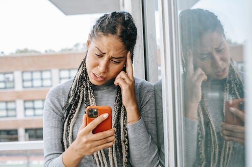 Tired black woman browsing mobile phone