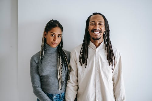 Delighted ethnic man with braids smiling widely while standing near girlfriend in casual clothes