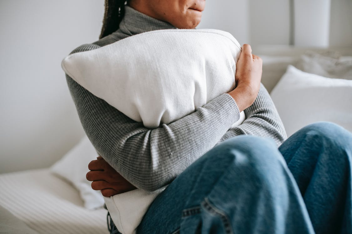 Crop anonymous worried ethnic female with soft pillow sitting on bed in sunlight at home