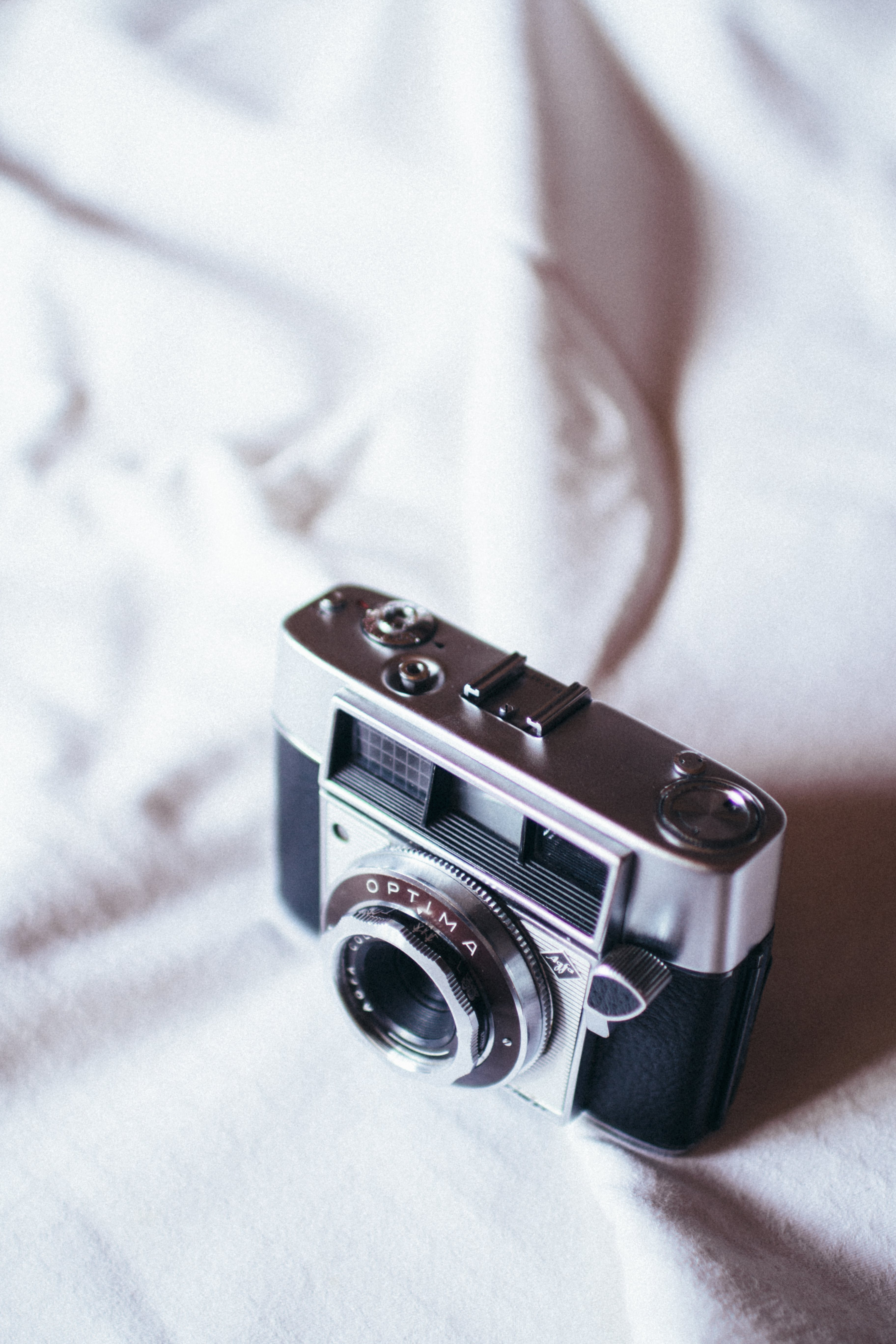 Black And Grey Camera On White Cloth