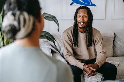 Black man talking to unrecognizable girlfriend in living room