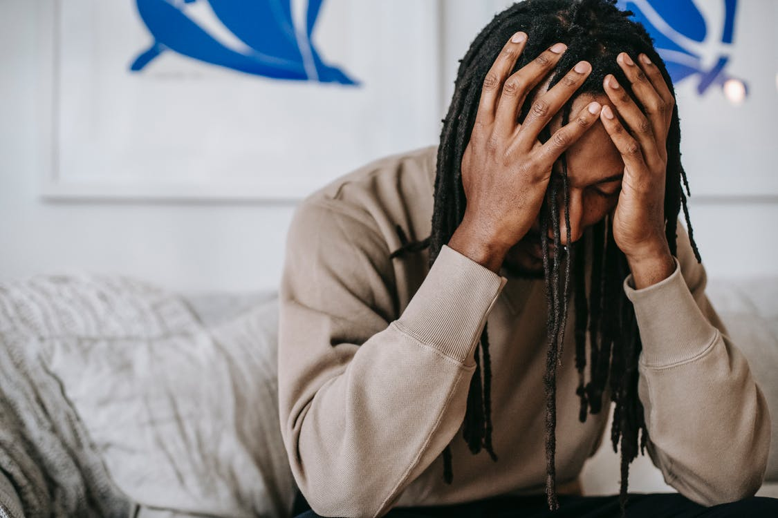 Crop anxious African American male with dreadlocks touching head with closed eyes on couch in house